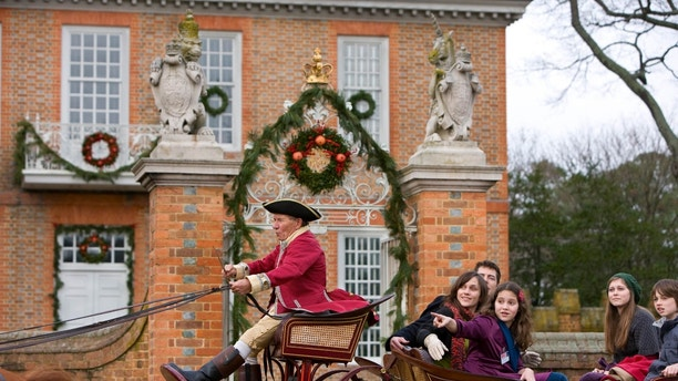Model released visitors tour on Palace Green in an open carriage during the Christmas Season. Colonial Williamsburg's Historic Area.