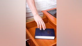 """""""reaching for a bible in  hotel drawer from the bed, Gideons Bible"""""""