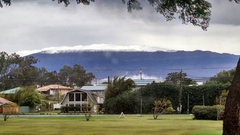 This photo provided by Grant Matsushige, an Instrumentation Specialist at the Canada-France-Hawaii Telescope, shows the summit of Mauna Kea on Hawaii's Big Island covered in snow as seen from Waimea, Hawaii on Thursday, Dec. 1, 2016. The National Weather Service in Honolulu has issued a winter storm warning for the summits of Hawaii's Big Island as wind and snow engulf the high peaks. (Grant Matsushige/Canada-France-Hawaii Telescope via AP)