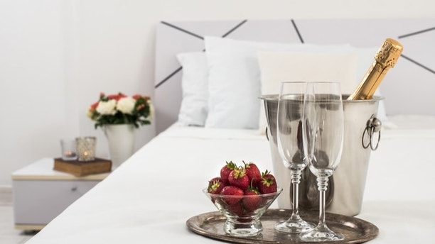 Champagne in bed in a hotel room, ice bucket, glasses and fruits on white linen