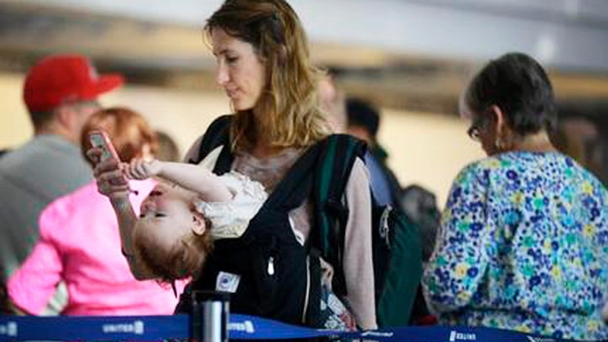 Ann Walden checks her phone as 15-month-old daughter Delphine plays while waiting in line after their flight to Baton Rouge was delayed at O'Hare International Airport in Chicago. There are several ways to distract and soothe little ones when traveling by air.