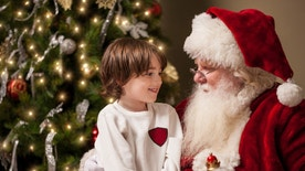 A young boy sits on Santa Claus' lap by a decorated Christmas tree in his living room. Santa has a real beard and the child looks at him with wonder, awe, and a hint of excitement.