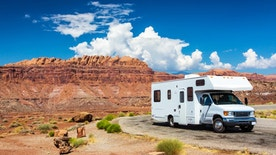 white RV / campervan in canyonlands USA with red cliffs and blue sky behind it