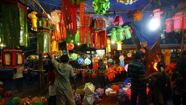 Indians buy lanterns from roadside stalls ahead of the Hindu festival of lights, Diwali, in Mumbai, India, Sunday, Nov. 11, 2012. People decorate their homes during this festival. (AP Photo/Rafiq Maqbool)
