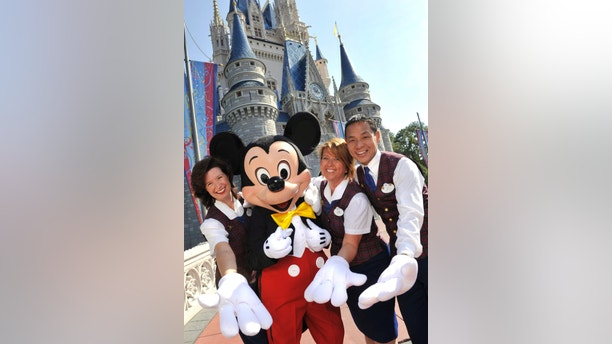 PLAID-CLAD MAGIC MAKERS:  Wearing their familiar plaid waistcoats, Walt Disney World V.I.P. Tour Guides (L-R): Danielle Warner, Laurie Sintay Fox and Les Tsui -- all three Celebration residents -- pose with Mickey Mouse in front of Cinderella Castle at the Magic Kingdom. (Gene Duncan, photographer)PLAID-CLAD MAGIC MAKERS:  Wearing their familiar plaid waistcoats, Walt Disney World V.I.P. Tour Guides (L-R): Danielle Warner, Laurie Sintay Fox and Les Tsui -- all three Celebration residents -- pose with Mickey Mouse in front of Cinderella Castle at the Magic Kingdom. (Gene Duncan, photographer)