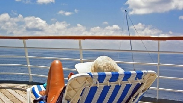 A woman sits on the upper deck of a cruise ship and overlooks the ocean