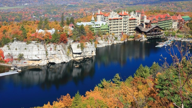 The blue sky and the Mohonk Mountain House resort reflected in Mohonk Lake and surrounded by sandstone cliffs and colorful Autumn trees in the Shawangunk Mountains of New York