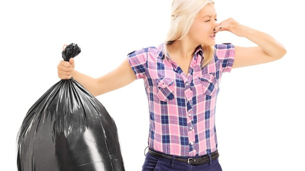 Woman holding a smelly garbage bag isolated on white background