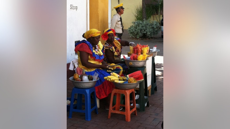 Dec. 26, 2013: Colorfully dressed vendors selling fruit in the old city of Cartagena.