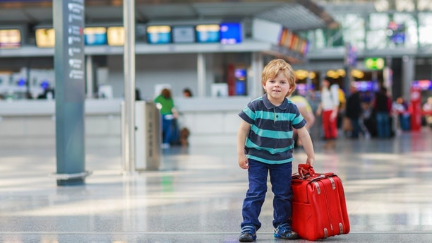Funny little boy going on vacations trip with suitcase at airport, indoors.