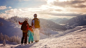 Happy family in winter clothing at the ski resort, winter time, watching at mountains in front of them