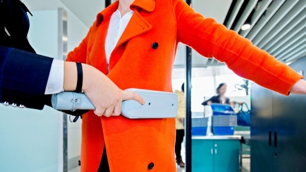 airport security check using a metal detector on a passenger.