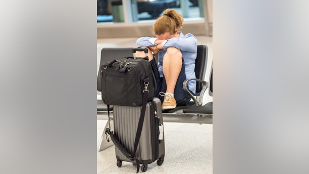 Frustrated Business Mature caucasian woman sitting at the airport passenger boarding terminal