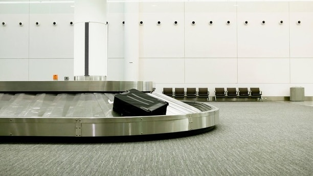 One lonely piece of luggage on an airport carousel.