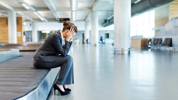 Businesswoman sits on an airport luggage conveyor belt with her head in her hands. Horizontal shot.