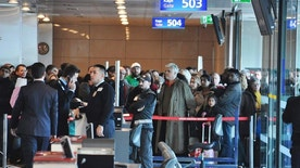 "Passengers of a Turkish Airlines flight to Toronto, Canada, wait at the boarding gate in Istanbul's Ataturk international airport, Saturday, Feb. 18, 2017. A Turkish Airlines plane in Istanbul was evacuated Saturday after a suspicious note was discovered in one of its bathrooms. The Turkish Airlines cabin crew found the words ""BOMB TO TORONTO"" on the bathroom's wall on Flight TK-17 during its pushback from the gate, a Turkish Airlines press official told The Associated Press. (DHA-Depo Photos via AP)"