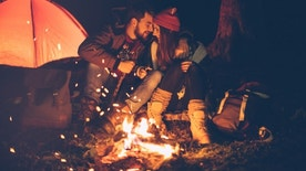 Young couple camping at mountain. Sitting in front of tent and warming by the fire. Wearing warm clothing. Winter night. Austrian Alps