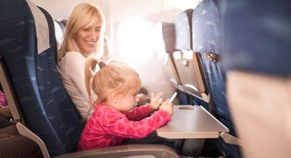 Little girl playing games on cell phone while traveling by plane with her mother. Focus is on little girl.