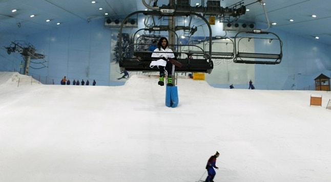 Visitors ski and ride in chairlifts in Dubai's indoor mountain-themed ski park, at Emirates mall in Dubai September 25, 2013. The 22,500 square-metre theme park features five runs, including a 400-metre ski slope that holds more than 6,000 tonnes of snow. The US$272-million resort is the first such project in the Gulf emirate, which is seeking to become a major tourism hub.  Reuters/Ahmed Jadallah (UNITED ARAB EMIRATES - Tags: BUSINESS SPORT SKIING TRAVEL) - RTX13Z8W