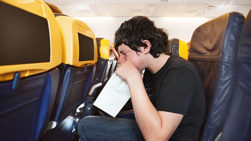 Boy getting sick in an airplane