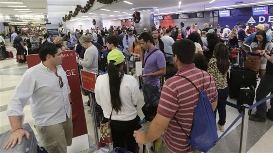 Passengers wait in line at the Delta airlines counter in terminal 2 at the Fort Lauderdale-Hollywood International Airport in Fort Lauderdale, Fla., on Saturday, Jan. 7, 2017.