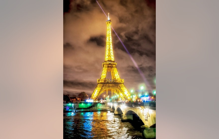 Paris, France - January 1, 2014: Paris, France, The Eiffel Tower illuminated at nightfall. Photographed from Avenue New York, with the view to Pont d'lena and river Siena. VIsible people