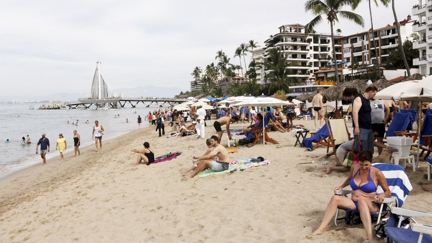 Tourists are seen along the beach resort of Puerto Vallarta, Mexico, December 31, 2015. REUTERS/Henry Romero - RTX20OU9