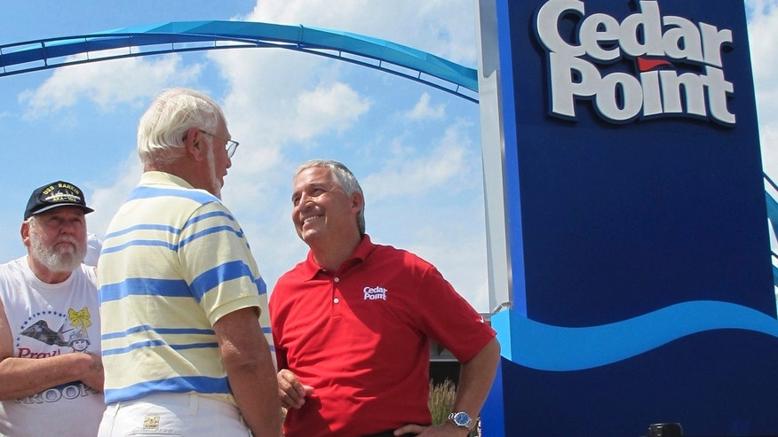 FILE - In this July 2, 2014, file photo, Matt Ouimet, chief executive of Cedar Fair Entertainment Co., greets a guest at Cedar Point amusement park, in Sandusky, Ohio.