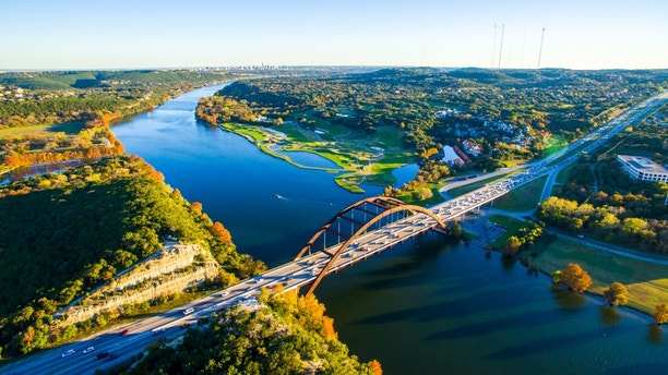 Aerial Pennybacker Bridge 360 Bridge From the Air as the leaves change colors and fall and the seasons change in central Texas. Fall turns to winter and Austin , Texas glows with bright colors of Fall and green and the Texas hill country looks amazing. This aerial breathtaking image of the Pennybacker Bridge built in 1984 and completes the Austin Vibe of West Texas Hill Country
