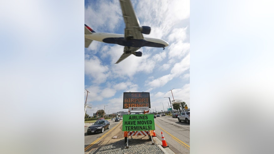 In this Thursday, May 11, 2017 photo, warning signs advise travelers that their airline's terminal may change as they approach Los Angeles International Airport. Numerous airlines will begin moving to different terminals or to new ticket counters in their current locations, beginning Friday night. The moves over several days are part of a massive overhaul of the heavily used airport and have been planned for months. (AP Photo/Reed Saxon)