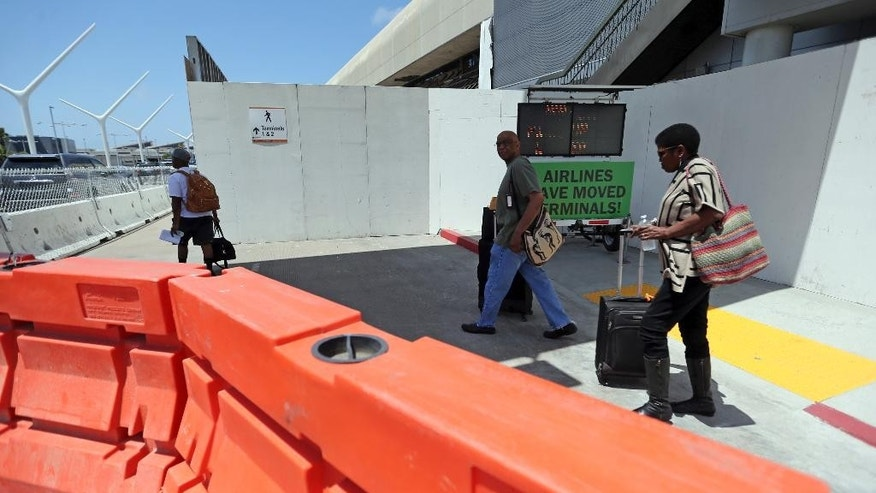In tis Thursday, May 11, 2017 photo, passengers navigate barricades and temporary walls at a construction area in Terminal 1 at Los Angeles International Airport. Numerous airlines will begin moving to different terminals or to new ticket counters in their current locations, beginning Friday night. The moves over several days are part of a massive overhaul of the heavily used airport and have been planned for months.  (AP Photo/Reed Saxon)