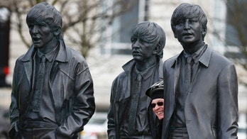 "A man poses for a photograph in front of a statue of The Beatles at the Pier Head in Liverpool, Britain March 9, 2016. The legendary record producer George Martin, known as ""the fifth Beatle"" for his work in shaping the band that became one of the world's most influential music forces, has died at the age of 90. REUTERS/Phil Noble  - RTS9ZTV"