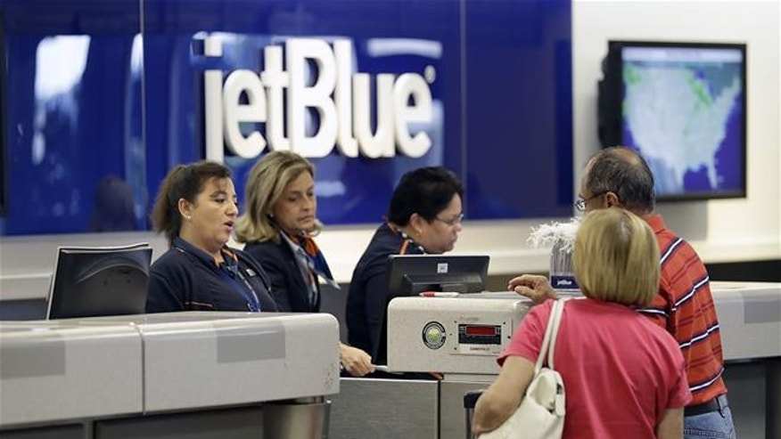 In this Wednesday, Oct. 26, 2016, photo, JetBlue Airways ticket agents assist passengers at the ticket counter at the Tampa International Airport in Tampa, Fla. JetBlue Airways Corporation reports financial results, Tuesday, April 25, 2017.