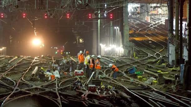 Amtrak workers repair tracks in New York's Penn Station, Monday, July 10, 2017. Amtrak has begun extensive repairs Monday to tracks and signals in Penn Station, which it owns and operates. Monday morning's rush got off to a slow start without any apparent problems. (AP Photo/Richard Drew)