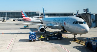 New York, USA - July 10, 2015: An America Airlines plane sitting at gate 39 at JFK airport late in the day as ground crew finish up before take off.