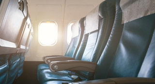 Interior of airplane with empty seats and sunlight at the window. Travel concept.