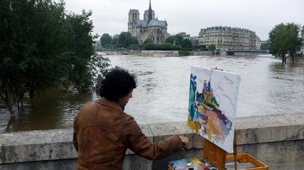 A man paints Notre Dame cathedral surrounded by the flooding Seine river in Paris, France Friday, June 3, 2016. Both the Louvre and Orsay museums were closed as the Seine, which officials said was at its highest level in nearly 35 years, was expected to peak sometime later Friday. (AP Photo/Jerome Delay)