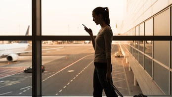 Female walking through the airport using her smartphone device.