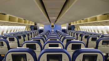 Airplane interior with rows of empty blue seats with video screens.