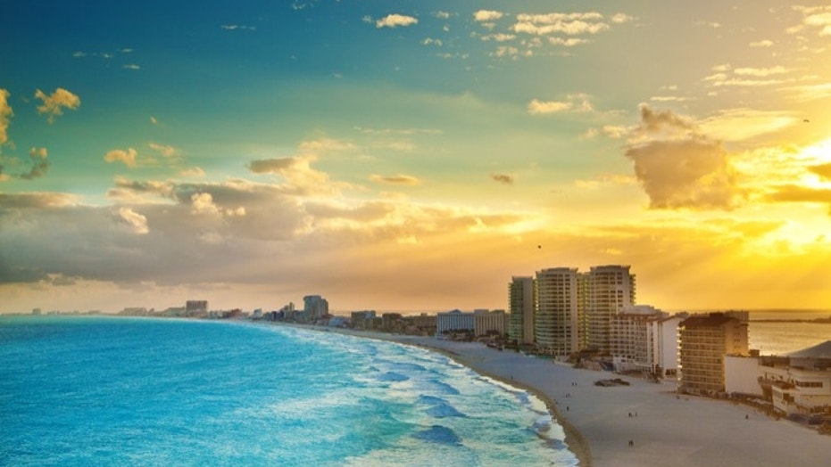 Subject: A panoramic view of the hotel district of Cancun at sunset. A popular tourist beach destination. The Yucatan Peninsula and the Riviera Maya in Mexico is a well developed vacation location with numerous hotels and entertainment districts.