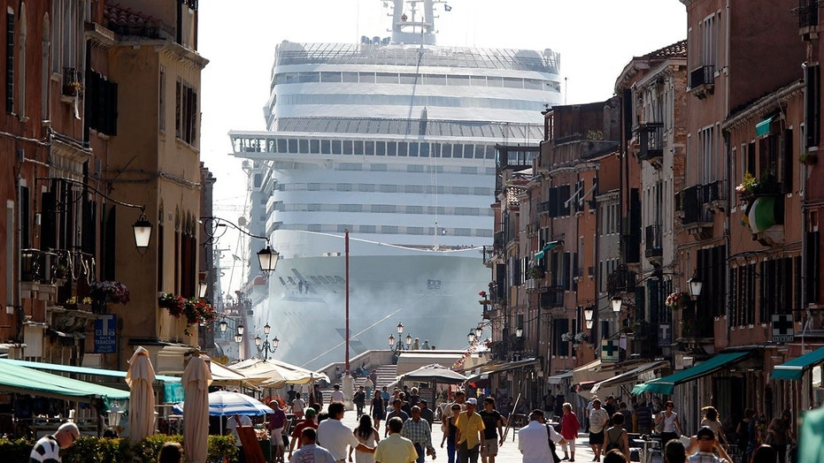 A cruise ship in Venice lagoon is seen looming over the city's streets.