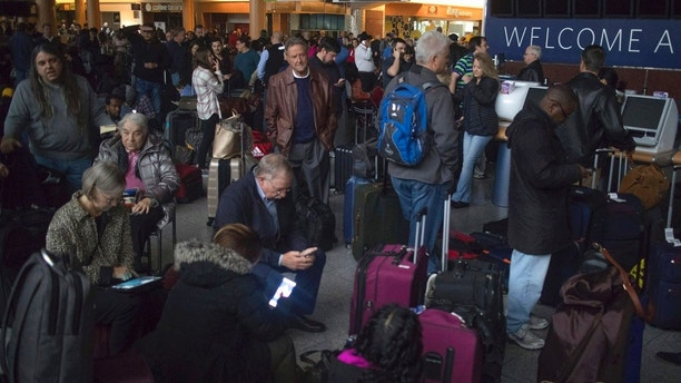 Passengers wait in a dark terminal at Hartsfield-Jackson International Airport, Sunday, Dec. 17, 2017, in Atlanta. A sudden power outage at the Hartsfield-Jackson Atlanta International Airport on Sunday grounded scores of flights and passengers during one of the busiest travel times of the year. (Steve Schaefer/Atlanta Journal-Constitution via AP)