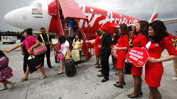 AirAsia staff greet passengers arriving from Kota Kinabalu to the Low Cost Carrier Terminal in Sepang outside Kuala Lumpur December 8, 2011, during its 10th year anniversary celebrations.  AirAsia started from two aircraft and three destinations in December 2001 to over 80 destinations in 24 countries and 107 aircraft groupwide, AirAsia press release stated.  REUTERS/Bazuki Muhammad (MALAYSIA - Tags: TRANSPORT) - GM1E7C816MO01