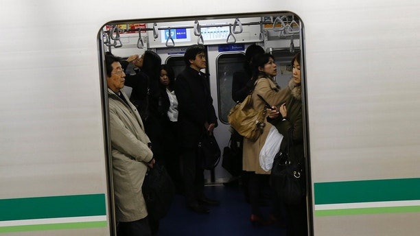 Passengers wait on a train at a subway station in Tokyo December 7, 2012, after a strong earthquake jolted northeastern Japan. A strong earthquake with a preliminary magnitude of 7.3 centred off the coast of northeastern Japan shook buildings as far as Tokyo and led to a tsunami warning for coastal areas of the northeast, public broadcaster NHK said on Friday. REUTERS/Kim Kyung-Hoon (JAPAN - Tags: DISASTER TRANSPORT) - GM1E8C71DM801