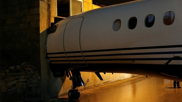 A privately-owned Dassault Falcon 7X business jet aircraft is seen after it was blown off the airport apron and into an adjacent building as strong winds hit the Maltese islands, according to local media, at Malta International Airport in Luqa, Malta, December 27, 2017. REUTERS/Darrin Zammit Lupi - RC1737690200