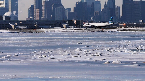 Ahead of an incoming winter snow storm, a Jet Blue flight waits to take off from Logan International Airport next to the frozen waters of the Atlantic Ocean harbour between Winthrop and Boston, Massachusetts, U.S., January 3, 2018.   REUTERS/Brian Snyder - RC1758EDA3D0