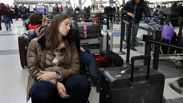 "An Avianca passenger rests as she waits for her flight at New York's John F. Kennedy Airport Terminal 4, Monday, Jan. 8, 2018. The Port Authority of New York and New Jersey said Monday it will investigate the water pipe break that added to the weather-related delays at Kennedy Airport and will ""hold all responsible parties accountable."" (AP Photo/Richard Drew)"