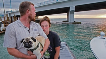 Tanner Broadwell holds his dog with Nikki Walsh at Madeira Beach, Fla., on Wednesday, Feb. 7, 2018.  The couple who abandoned their workaday lives to buy a sailboat for a once-in-a-lifetime adventure instead lost almost everything when it sank on day two of their journey off Florida. They escaped injury when the 28-foot boat hit something and capsized Wednesday in the Gulf of Mexico near Madeira Beach. (Jim Damaske/Tampa Bay Times via AP)