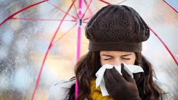 Woman with cold or flu coughing and blowing her nose with a tissue under autumn rain. Brunette female sneezing and wearing warm clothes.
