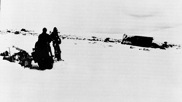 The wreckage of an Air New Zealand DC-10 lies on the side of Mount Erebus in the Antarctic, Nov. 30, 1979. Pieces of the plane covered an area of 600 x 60 yards. On the left are the wheels of the aircraft and two of the search team. On the right is the largest piece of wreckage, the fuselage. (AP Photo)